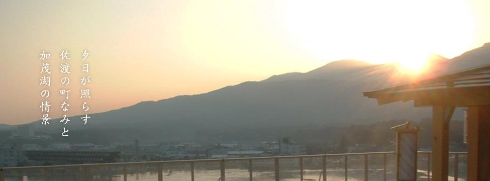 夕日が照らす佐渡の町なみと加茂湖の情景